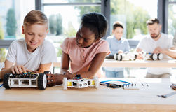 Girl examining the wheel of her friends robotic vehicle. Piece of advice. Pretty pre-teen girl inspecting her friends robotic vehicle while her teacher helping Stock Photography
