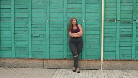 A girl with excess weight next to a green wall. Portrait of a young girl overweight in the city Park on the background of a green wooden fence. Slow motion stock video