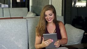 Girl with excess weight sits in a cafe with tablet. A beautiful girl with excess weight sits in a restaurant with a tablet. The fat girl is resting in a street stock video