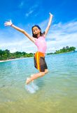 girl excited, jumping in the air at the beach Stock Images