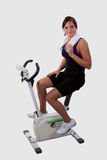 Girl on exercise bike. Attractive young brunette woman wearing workout attire sitting and pedalling on a stationary exercise bike stock photo