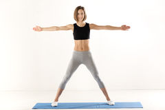 Girl Exercise With Outstretched Arms. Athletic build woman in sports clothes with arms outstretched, standing on the mat for exercise and with a smile looking at Royalty Free Stock Images