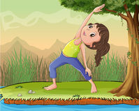 A girl exercise under a tree Stock Photography