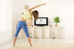 Girl Exercise, Watching TV Royalty Free Stock Photos
