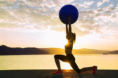 Girl exercise by the water with ball. Stock Image