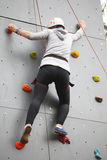 Girl exercises on indoor rock climber Stock Photos