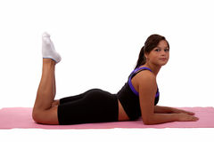 Girl exercising. Attractive young teen aboriginal ethnicity brunette girl wearing fitness attire laying flat on stomach with legs bent on a pink yoga mat over stock image