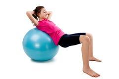 Girl exercising. Using ball on white background Royalty Free Stock Image