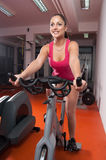 Girl exercising on the bicycle in the gym Royalty Free Stock Images