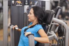 Bodybuilding. woman exercising in gym with exercise-machine arms back and shoulders. Girl exercising in gym with exercise-machine arms back and shoulders Royalty Free Stock Images