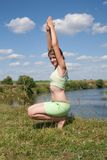 Girl exercising on meadow against river Stock Image
