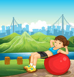A girl exercising near the river across the tall buildings Stock Images