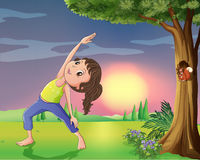 A girl exercising near a tree with squirrel Royalty Free Stock Photos