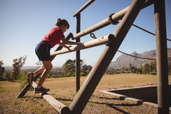 Girl exercising on outdoor equipment during obstacle course. In boot camp royalty free stock image