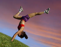 Girl exercising outdoors. Against sunset Stock Photography