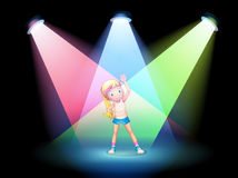 A girl exercising on the stage with spotlights Royalty Free Stock Image