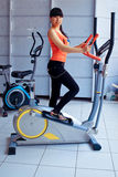 Girl exercising at the  on stepper machine Stock Photos