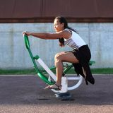 Girl exercising on training machine for bodybuilding. Young Papuan woman - smiling girl sitting and exercising on green and white training and exercise machine Stock Photo