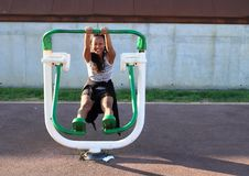 Girl exercising on training machine for bodybuilding. Young Papuan woman - smiling girl standing and exercising on green and white training and exercise machine Royalty Free Stock Photo