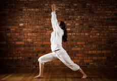 Girl exercising yoga against brick wall Royalty Free Stock Image