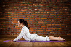 Girl exercising yoga against brick wall Stock Photography