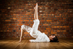 Girl exercising yoga against brick wall Stock Images