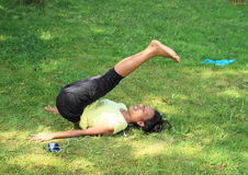 Girl exercising yoga on meadow Royalty Free Stock Photos