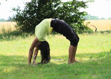 Girl exercising yoga on meadow Royalty Free Stock Photography