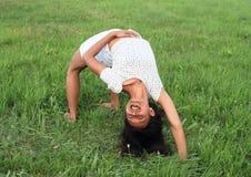 Girl exercising yoga on meadow Stock Image