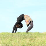 Girl exercising yoga on meadow. Tropical girl - woman in black pull, pantyhoses and colorful skirt exercising yoga - upward bow or wheel pose on green grass with Stock Photos
