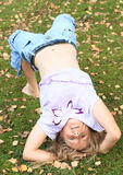 Girl exercising yoga on meadow. Young girl - hairy blond kid with naked belly exercising yoga - upward bow or wheel pose and failed on green grass of meadow with Royalty Free Stock Photography