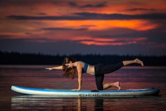 Girl exercising yoga on paddleboard in the sunset on scenic lake Velke Darko stock image