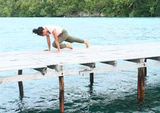 Girl exercising yoga pose on jetty by sea stock photography