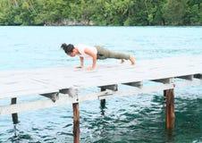 Girl exercising yoga pose plank on jetty by sea. Young Papuan woman - pretty girl exercising yoga pose plank on wooden jetty above sea in Raja Ampat, Papua Barat royalty free stock photos
