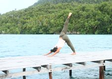 Girl exercising yoga pose three-legged downward dog on jetty by sea stock images