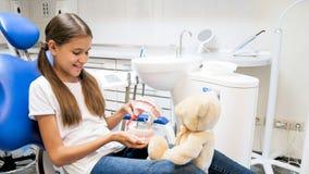 Cute girl explaining to teddy bear how to properly clean teeth. Girl explaining to teddy bear how to properly clean teeth royalty free stock photography
