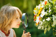 Girl exploring flowers through the magnifying glass Stock Image