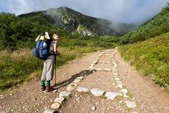 Girl exploring the mountains. Backpacker girl tourist exploring the Tatra mountains national park, Poland Stock Photo