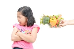 Girl with expression of disgust against vegetables. Asian child girl with expression of disgust against vegetables isolated on white background, Refusing food Royalty Free Stock Photo