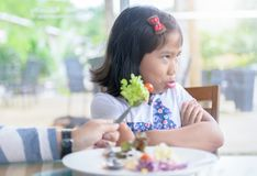 Girl with expression of disgust against vegetables. Asian child girl with expression of disgust against vegetables in restaurant, Refusing food concept Stock Image