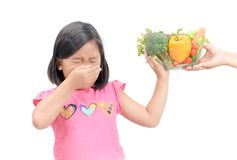 Girl with expression of disgust against vegetables. Asian child girl with expression of disgust against vegetables isolated on white background, Refusing food Stock Photo