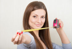 Girl extending a tape measure out Stock Photos