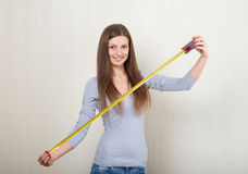Girl extending a tape measure out Royalty Free Stock Image