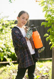 Girl exterminating insects in garden with toxic spray Royalty Free Stock Photography