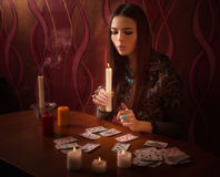 Girl extinguishes candles after divination. Indoor Stock Photos