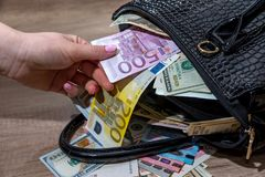 Girl extract dollars from the full-packed bags of money.  Royalty Free Stock Photo