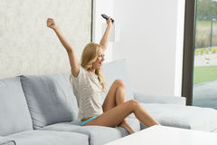 Girl exulting on sofa. Pretty blonde woman sitting with naked legs and panties on sofa, exulting with happiness  expression watching television and taking remote Stock Photography