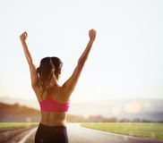 Girl exults in victory sign. Young woman enjoys the freedom and joy of living outdoors Royalty Free Stock Images
