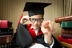 Girl in eyeglasses and graduation cap pointing at camera Stock Photography