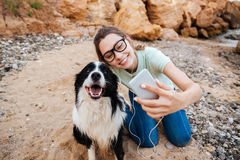 Girl in eyeglasses taking selfie with her dog on smartphone. Smiling young cheerful girl in eyeglasses having fun with her dog at the beach and taking selfie Stock Photos